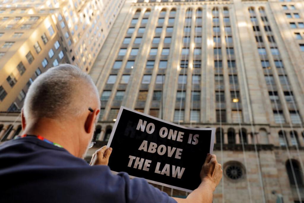 """""""Niekas nėra aukščiau už įstatymą"""" – skelbiama D.Trumpo apkaltą remiančio demonstranto plakate Niujorke."""