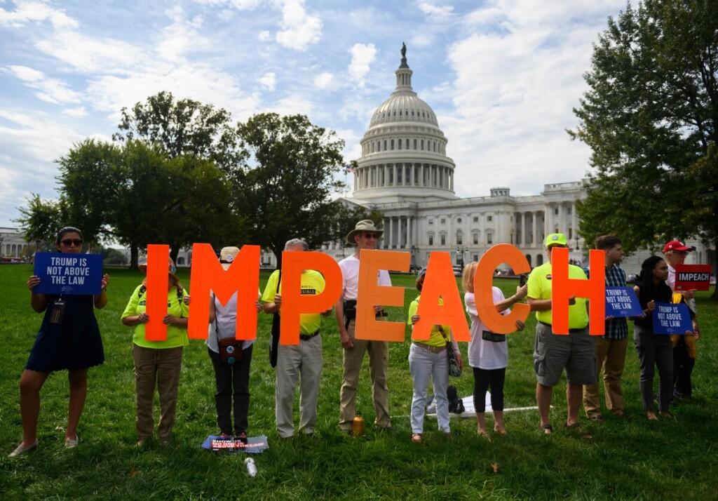 """Prie JAV Kongreso rūmų susirinkę žmonės laiko iškėlę žodžio """"Apkaltinkit"""