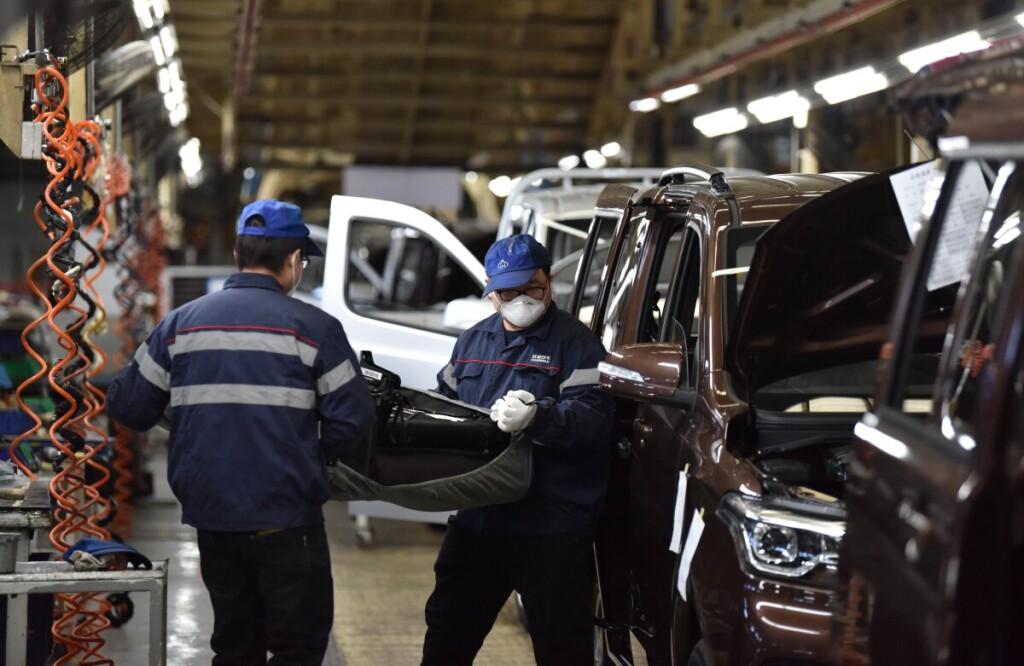 """Valstybinės įmonės """"Chang an Automobile"""" Hebėjaus provincijoje rytinėje Kinijoje darbininkai cechuose dirba su apsauginėmis kaukėmis."""