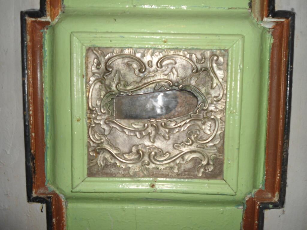 Sidabrinė plokštelė su pėdos atvaizdu koplytėlės viduje.