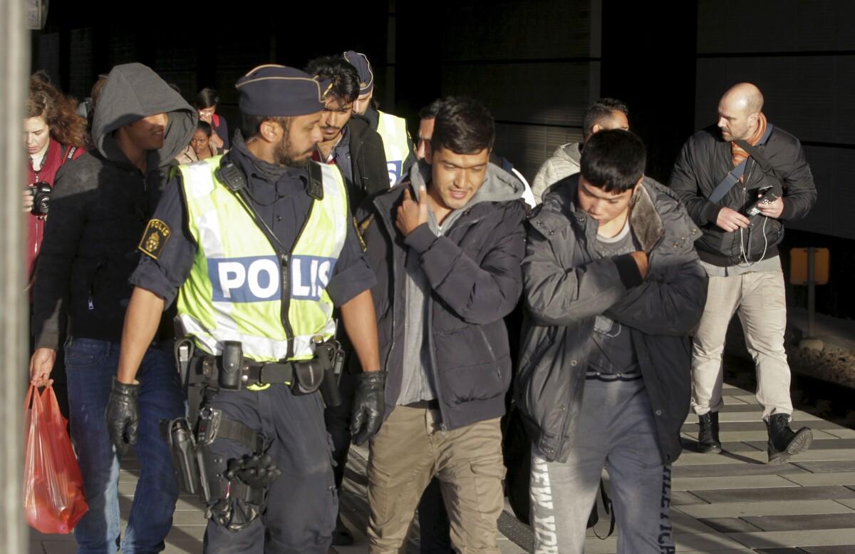 Policijos pareigūnas lydi traukiniu iš Danijos į Švediją atvykusius imigrantus.